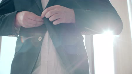 iyi giyimli : Buttoning a jacket. Stylish man in a suit fastening buttons on his jacket preparing to go out. Stok Video