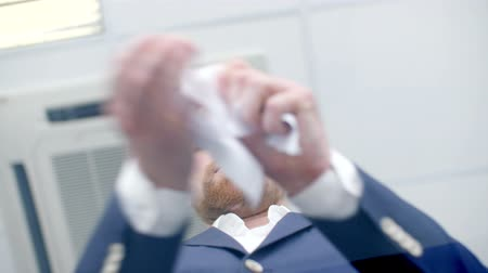 скрепки : Angry businessman tearing a paper in pieces. shoot from below.