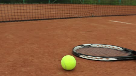 tennis game : A tennis racket and new tennis ball on a freshly painted tennis court
