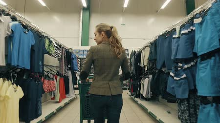 roupas : Young blond woman chooses clothes in supermarket Stock Footage