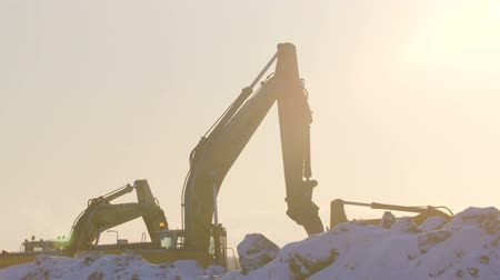 levelling : RUSSIA ST.PETERBURG- 28 FEBRUARY: Excavators digging the ground in winter sunset