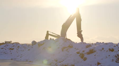 levelling : Excavators digging the ground in winter sunset
