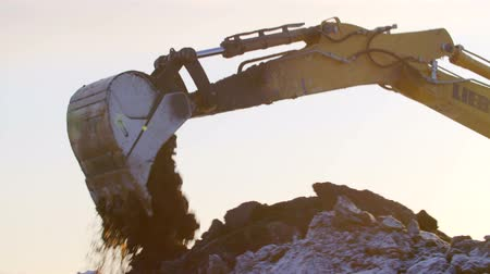экскаватор : Excavator digging the ground in winter sunset Стоковые видеозаписи