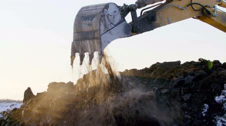 levelling : Excavator digging the ground in winter sunset Stock Footage