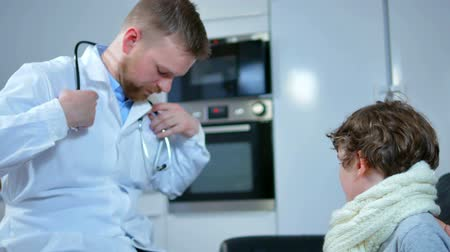 vyšetření : home doctor came to sick boy and his mother. he examines a child and records readings in notebook