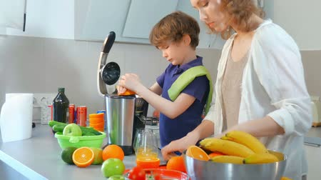 mutfak malzemesi : Young Caucasian Mother and Child Homemade Fresh Orange Juice in Kitchen with Electric Juicer Stok Video