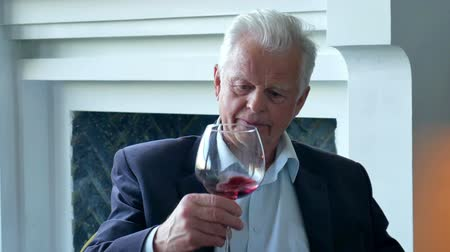 züppe : elderly man drinking wine at home and smile