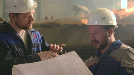 warsztat : portrait of two engineers explore and discuss project in heavy industry factory. welding background