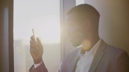 barato : Young black man in suit using smartphone standing by window in ghetto office in the sun Stock Footage