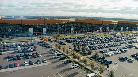 множество : Big parking lot full of cars near large exhibition center