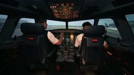 belirleme : Two caucasian male pilots in the cockpit or flight deck of a passenger airplane work with check list and prepare for taxiing on the runway before take off on. At the background of airport buildings, runway and other aircrafts