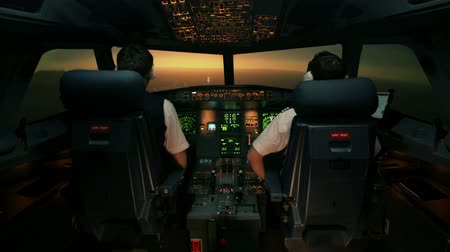 tényező : Modern passenger aircraft during descent. Sunset view from the cabin of modern plane to the Airport ruway with lighting. Two professional male pilots in the cockpit or flight deck control airplane
