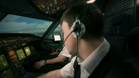 aircrew : Side view of two professional pilots in the cockpit or flight deck of a modern passenger airplane turn on and switch controls panel of aircraft. Shot at training center