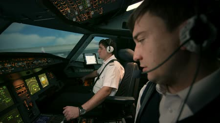 pilot in command : Side view of cabin. Captain and co-pilot perform radio communication with tower of airport before turn on power of engines of aircraft. Ready to take off and departure.