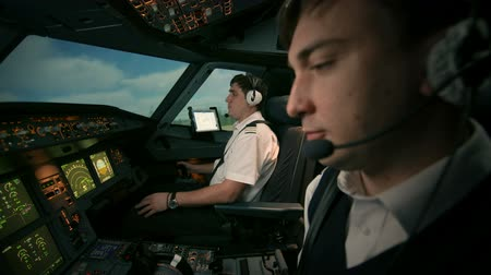 first officer : Side view of flight deck during takeoff. Airplane is running on the runway of airport and then take off and departure. Pilot-In-Command, co-pilot in the cockpit of modern passenger aircraft