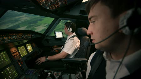 aircrew : Two professional pilots in the cockpit or flight deck of a perform turn to set the course of flight. At the background of green fields. Domestic flight