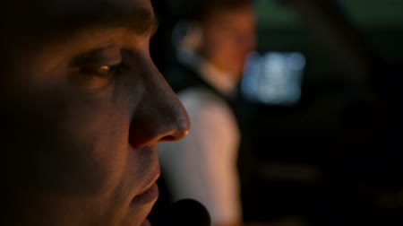 belirleme : Close shot of two professional pilots at the cockpit of modern passenger airliner. Aircraft taxiing at the runway. Captain communicates with air traffic controller at tower. Focal point changes or moves from one man to other. Cinematic shot
