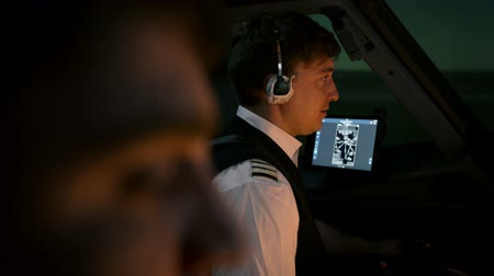 belirleme : Close shot of two professional pilots at the cockpit of modern passenger airliner. Aircraft taxiing at the runway. Captain talks by radio with air traffic controller at tower. Shot at night or early morning. End of journey.