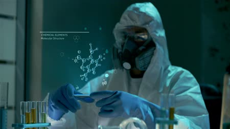 engineered : Professional scientist in protective glasses, gas mask and gloves holds virtual computer with animated 3D model of complicated organic molecule. Chemist looks at data in hologram. Studying of experiment results in modern futuristic chemical laboratory. Stock Footage