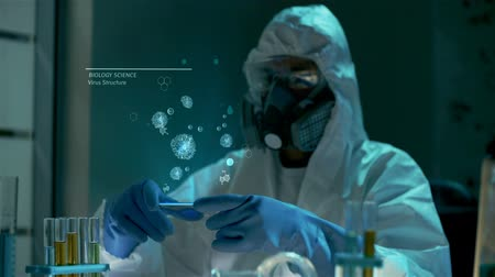 engineered : Examination of new dangerous virus strain. Global work to reduce epidemy, diseases and illness in the world. Bio scientist in protective lab clothes holds futuristic graphic hologram interface with 3D animated models of virus samples at biological researc Stock Footage