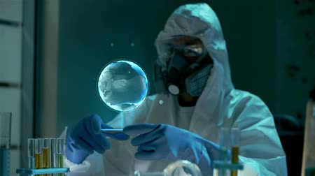 engineered : Scientist of bio engineering technology or chemistry in protective clothes is looking at blue glow hologram of Earth Planet spinning globe floating in air against him. Shot can be used to demonstrate the fragile balance of the world, a powerful relations  Stock Footage