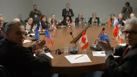 protrude : Canadian leader at international summit. Flag of Canada, white paper, pencil and microphone. Political delegates from different countries of G20 applaud the speaker. High-level discussion of policy and financial stability.