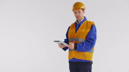 prospective : Young good looking male builder or construction worker with tablet PC looks at camera, smiles and raises up the thumb Stock Footage
