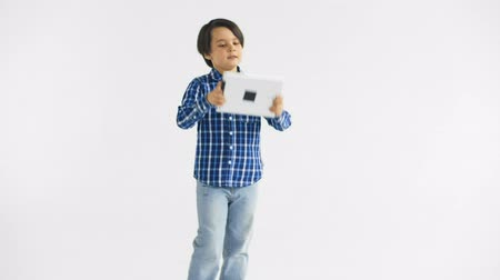 bewilderment : Cute little boy with dark hair plays game on the tablet PC at white background