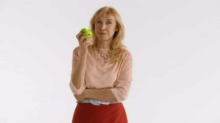 stáří : Full isolated portrait of a handsome elderly woman in a red skirt, biting a green apple standing at white background Dostupné videozáznamy