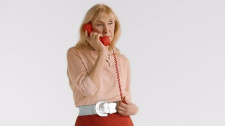 charges : Beautiful elegant elderly blond woman uses red landline phone handset and talks with her friend. Lady of elegant age on white background