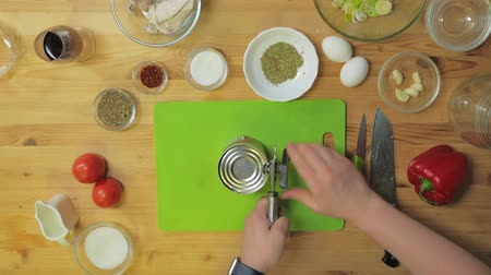 abridor : Top view. A man opens a tin of beans in the kitchen before dinner Stock Footage