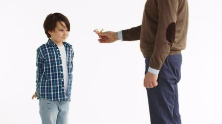 sarıcı : The father rewards the son for good behavior and gives him candy