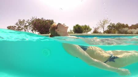 stroke : Beautiful happy woman swims in the pool. Shooting from underwater