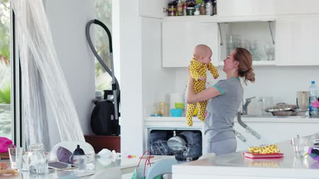 házimunkát : Woman housewife on maternity leave in the kitchen holding his newborn daughter