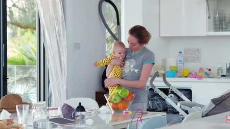 házimunkát : Housewife multitasking at home with her newborn daughter