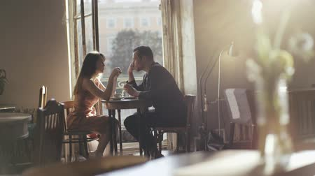 namorado : Romantic couple drinking coffee at a cafe table. Happy couple talking in a cafe