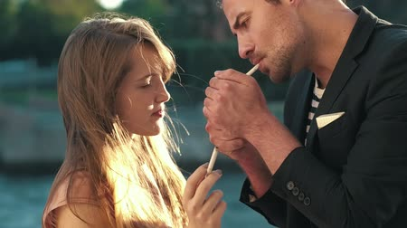 papieros : Man and a woman smoking cigarettes together. Cigarette lighter in hands man. Wideo