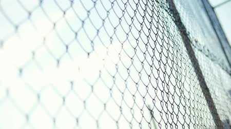 kötü : Blows on mesh fence with mens hands. Angry bald man beats hands on a grid fence