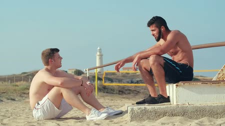 гей : Two athletes in shorts near the sea lighthouse. Two friends on summer holiday have fun at the background of lighthouse