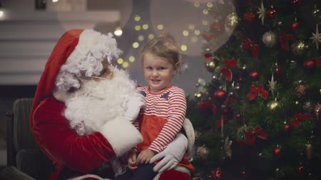 good new year spirit : Kind Santa Claus playing with little girl sits on his knee in Christmas eve