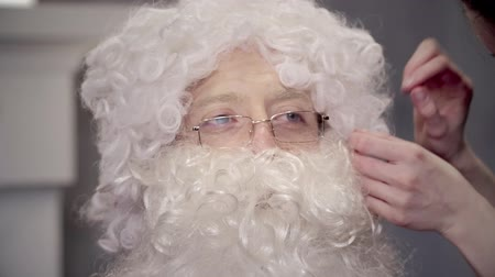 peruka : Hands make up artist straightens hair on wig Santa Claus for filming movie Wideo