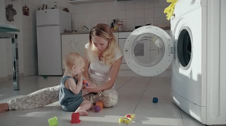 nanny holding : Young mother playing with toys with daughter on floor opposite washing machine Stock Footage