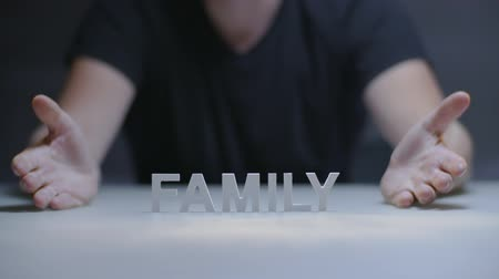 protects : Man hands showing word family composed from white letters on gray background Stock Footage