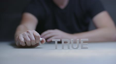ídolo : Man hand taking word not in composition not true by letters on gray background Stock Footage