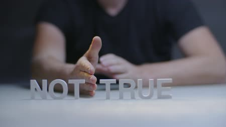 verdadeiro : Male hand transforms word not true to true on gray background