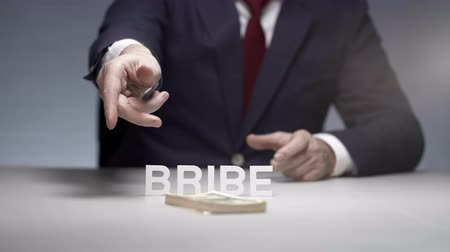 przeszczep : Businessman throwing pack of money on table. Illegal bribe to oligarch Wideo