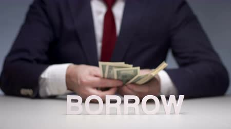 povinnost : Businessman hands consider banknote from a bundle of money for borrow to partner