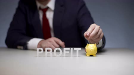 осуществлять : Male hand laying coin in pigs money box. Accumulation profit in modern business