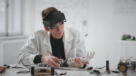 implantation : Man researcher repairing and constructing with tools robotic hand prosthesis Stock Footage