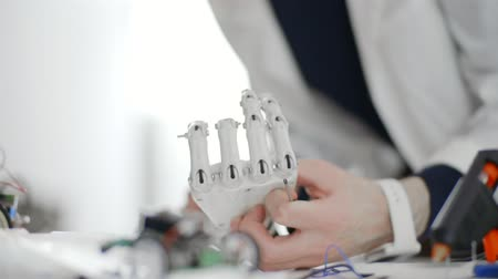 implantation : Man researcher in protective glasses using tools constructing robotic hand
